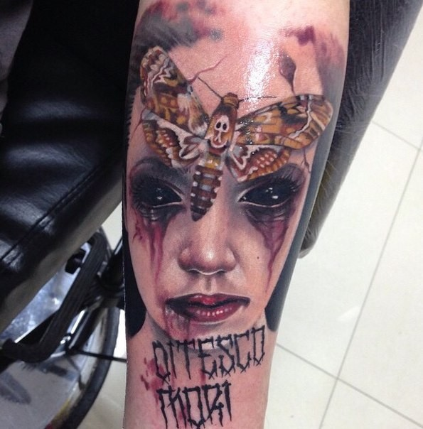 Horror style creepy looking arm tattoo of demon woman with butterfly
