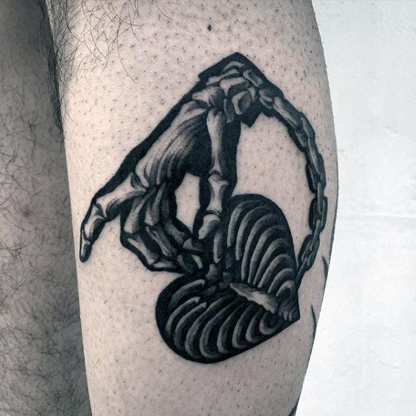 Illustrative style black and white leg tattoo of chained bone hand and heart