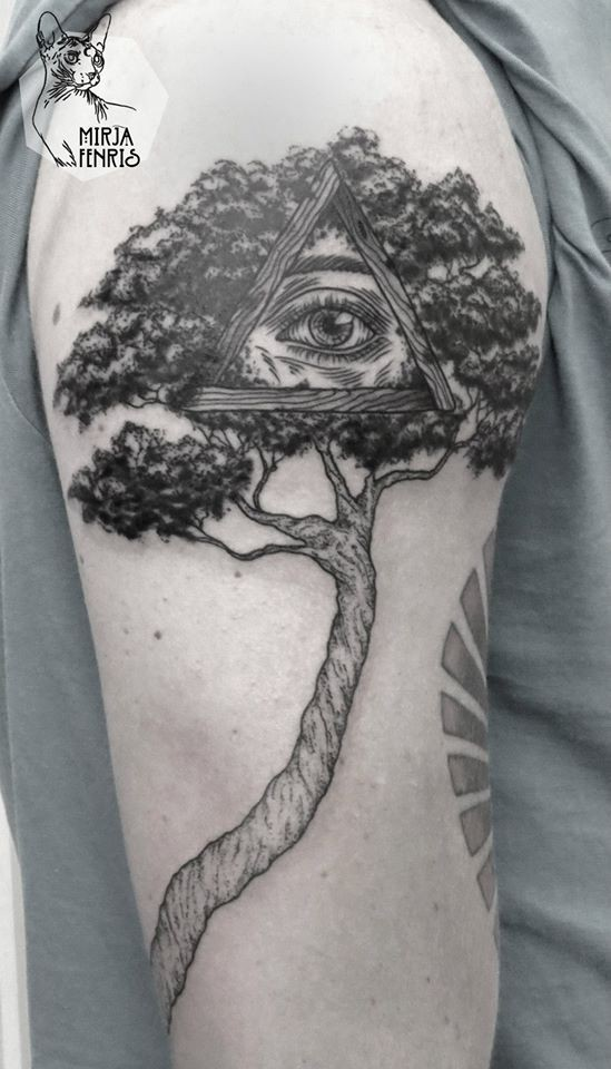Illustrative style black ink shoulder tattoo of big tree with mysterious eye