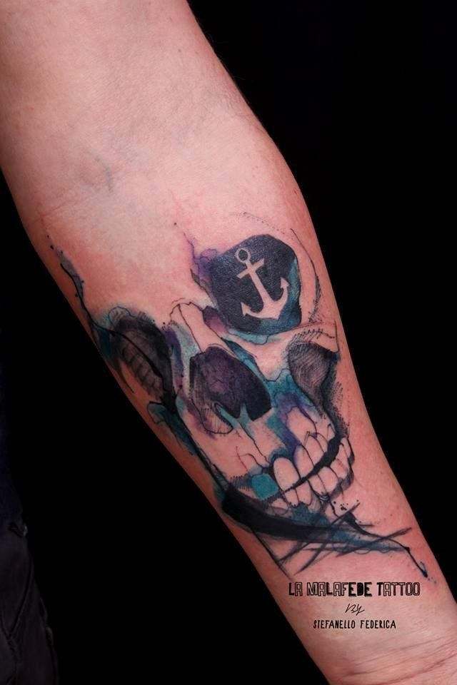 Illustrative style colored forearm tattoo of human skull stylized with anchor