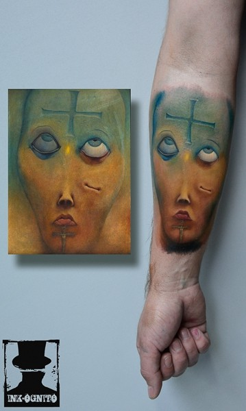 Illustrative style colored forearm tattoo of creepy face with cross