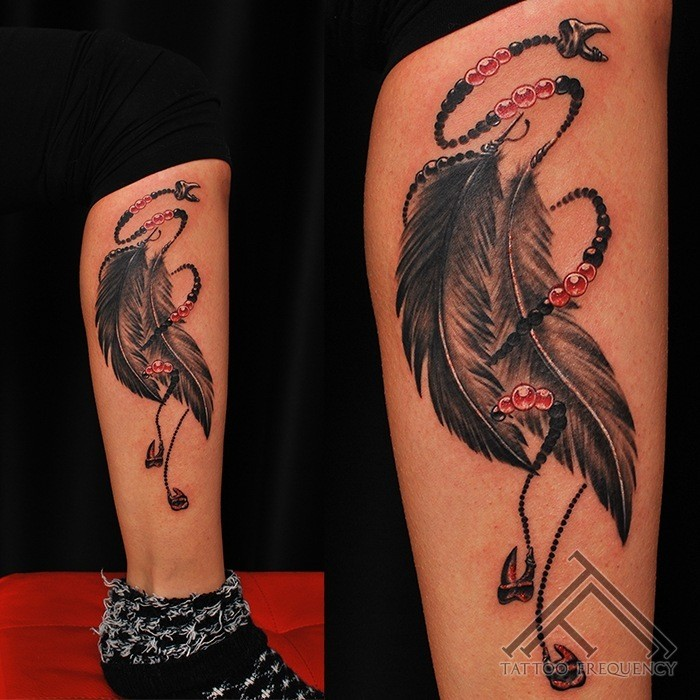Illustrative style colored leg tattoo of feather totem