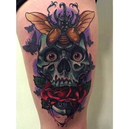 Illustrative style colored thigh tattoo of creepy skull with rose and bug