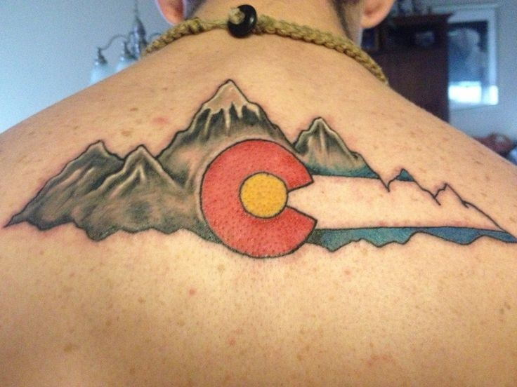 Illustrative style colored upper back tattoo of mountains and national flag