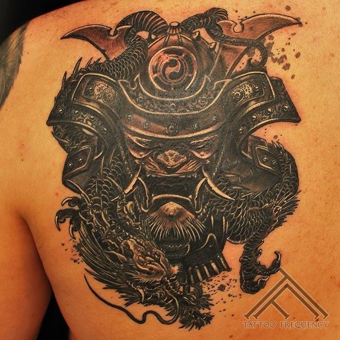 Illustrative style detailed scapular tattoo of large samurai mask and dragon