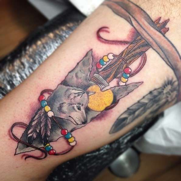 Incredible 3D style old arrow head tattoo stylized with wolf and feather