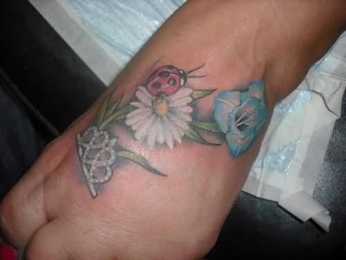 Ladybug and flowers tattoo on arm