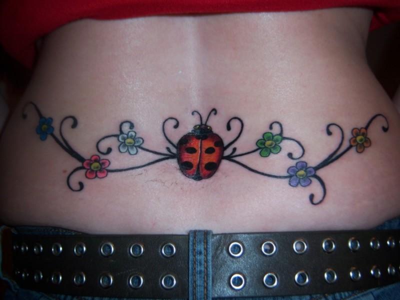 Ladybug and flowers tattoo on lower back