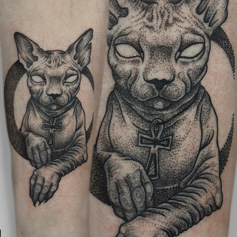 Large dot style arm tattoo of mysterious sphinx cat with large cross
