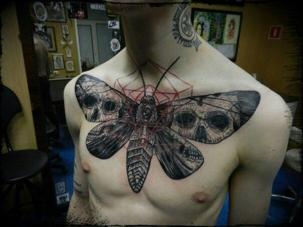 Large illustrative style chest tattoo of big butterfly stylized with human skulls