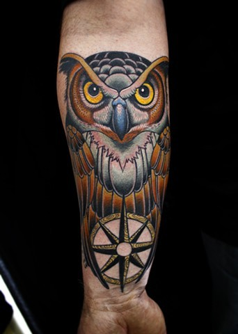 large illustrative style colored owl tattoo on forearm with nautical star