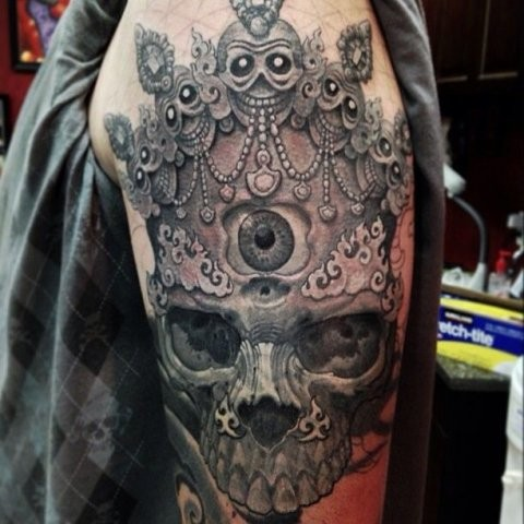 Large illustrative style shoulder tattoo of human skull with crown and eye