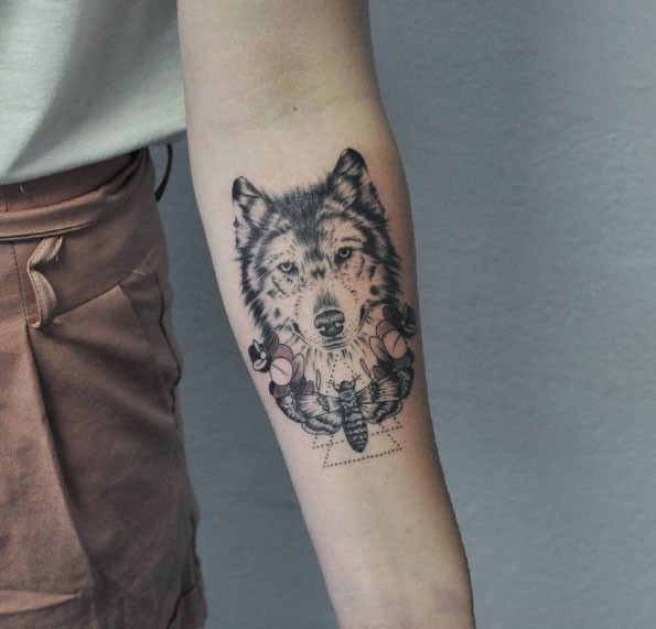 Lifelike detailed forearm tattoo of wolf with big butterfly