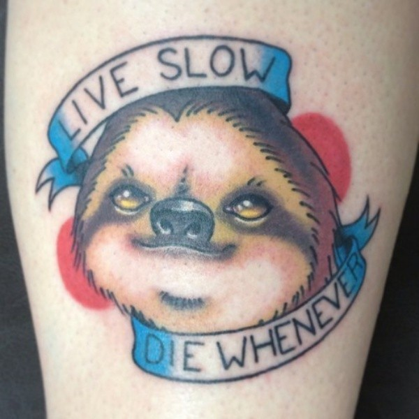 Little colored funny sloth with lettering tattoo on arm