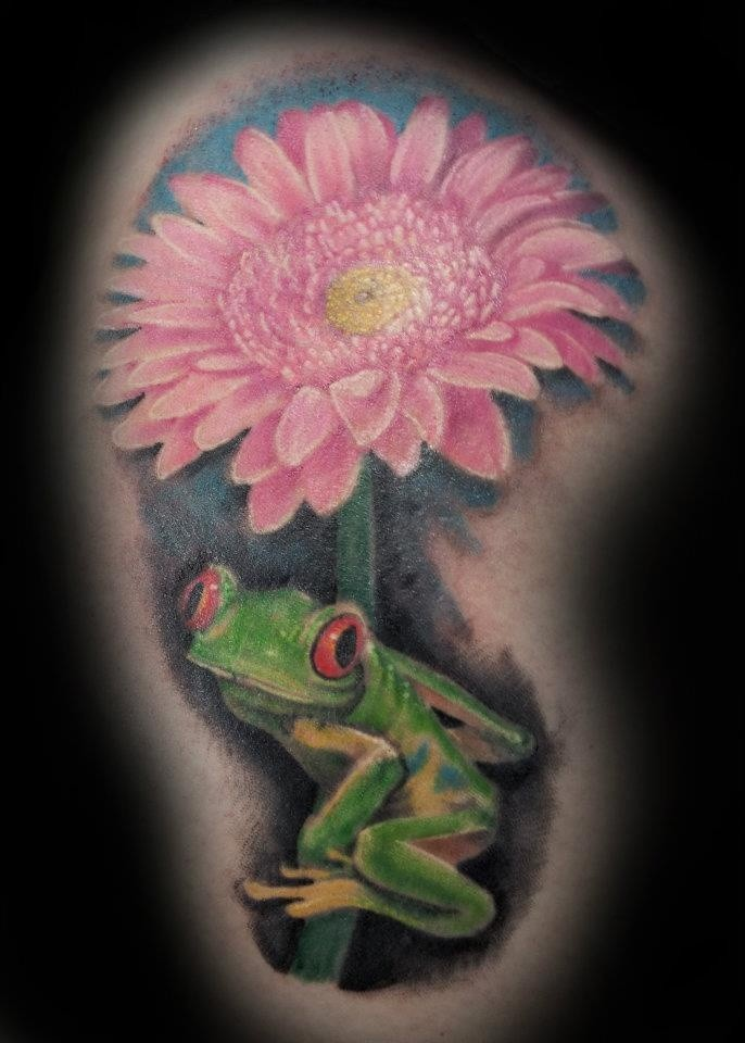 Little green frog sitting on a pink flower tattoo