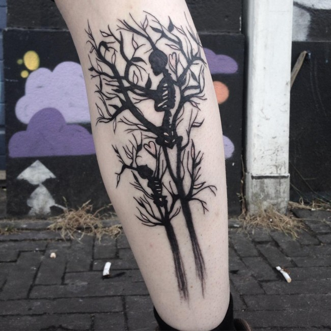 Marvelous black ink leg tattoo of blooming tree with skeleton family