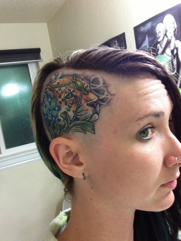 Medium size illustrative style head tattoo of leopard with jewelry and flower