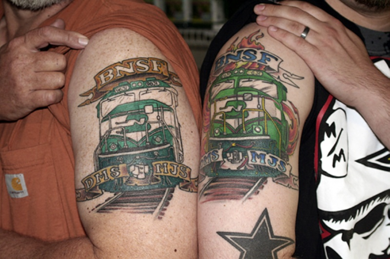 Memorial style colored upper arm tattoo of trains with lettering