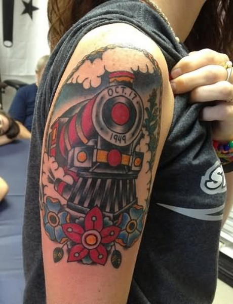 Memorial style colored upper arm tattoo of train with lettering and flowers