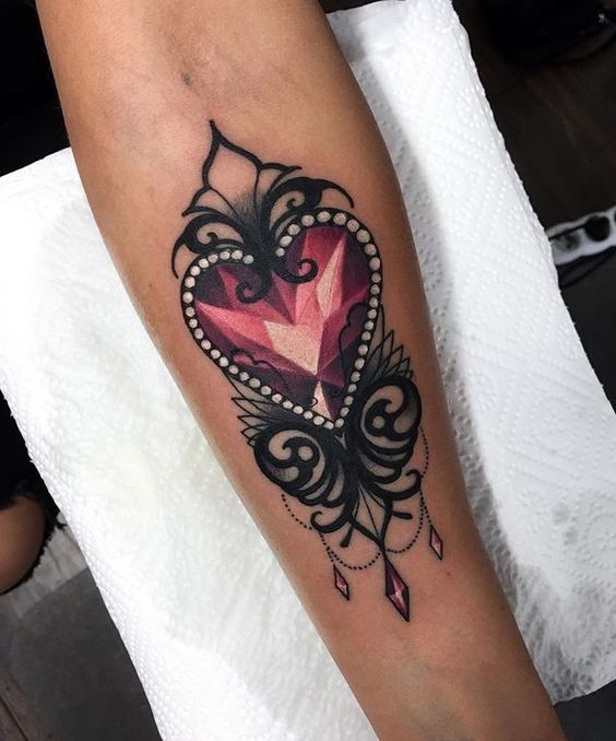 Modern style colored forearm tattoo of heart shaped diamond painted by Jenna Kerr
