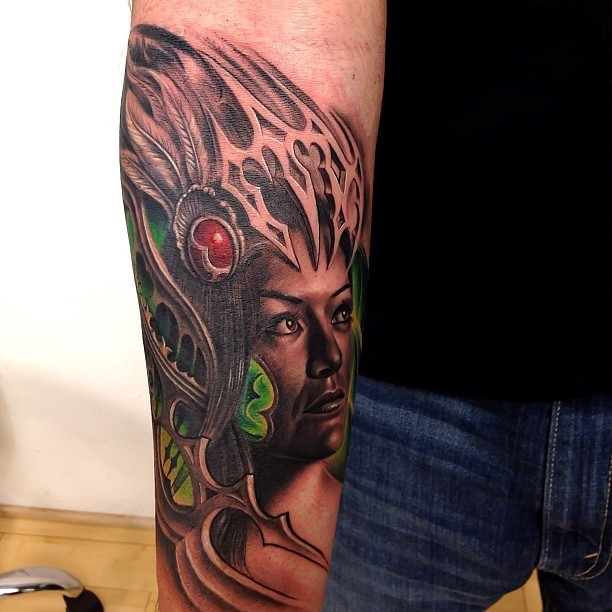Modern style colored forearm tattoo of tribal woman with helmet