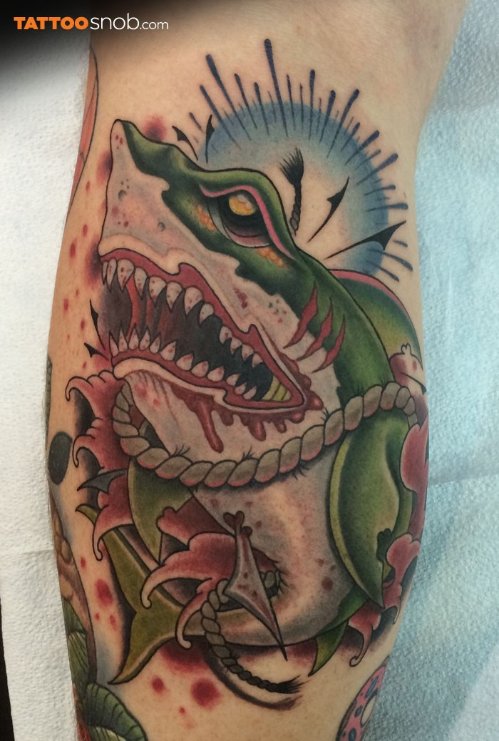 Modern traditional style bloody leg tattoo of creepy shark with rope