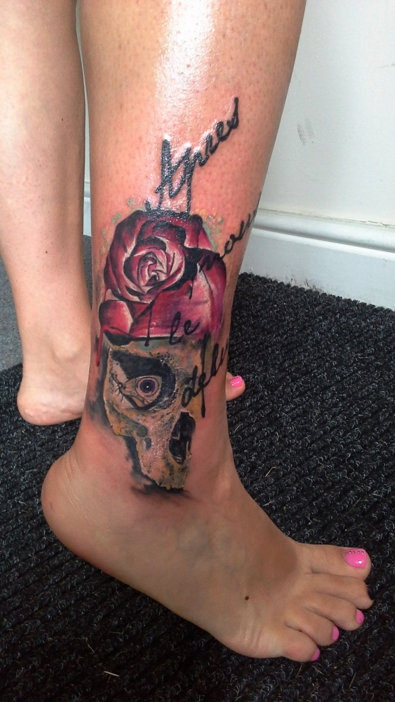 Modern traditional style colored ankle tattoo of human skull with rose and lettering