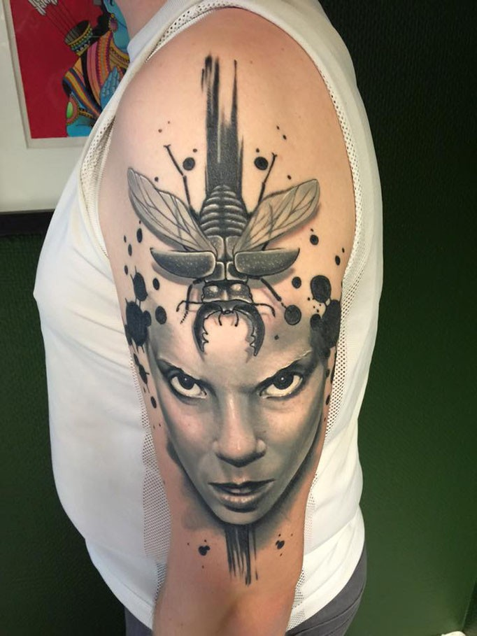 Modern traditional style detailed shoulder tattoo of woman face with big bug