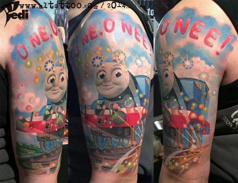 Multicolored cartoon Thomas train funny tattoo with lettering on shoulder
