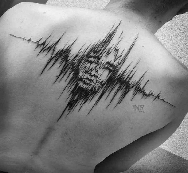 Music wave shaped black ink upper back tattoo painted by Inez Janiak stylized with human face