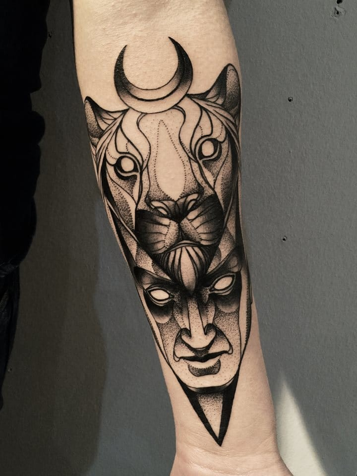 Mysterious blackwork style painted by Michele Zingales forearm tattoo of human face with lion