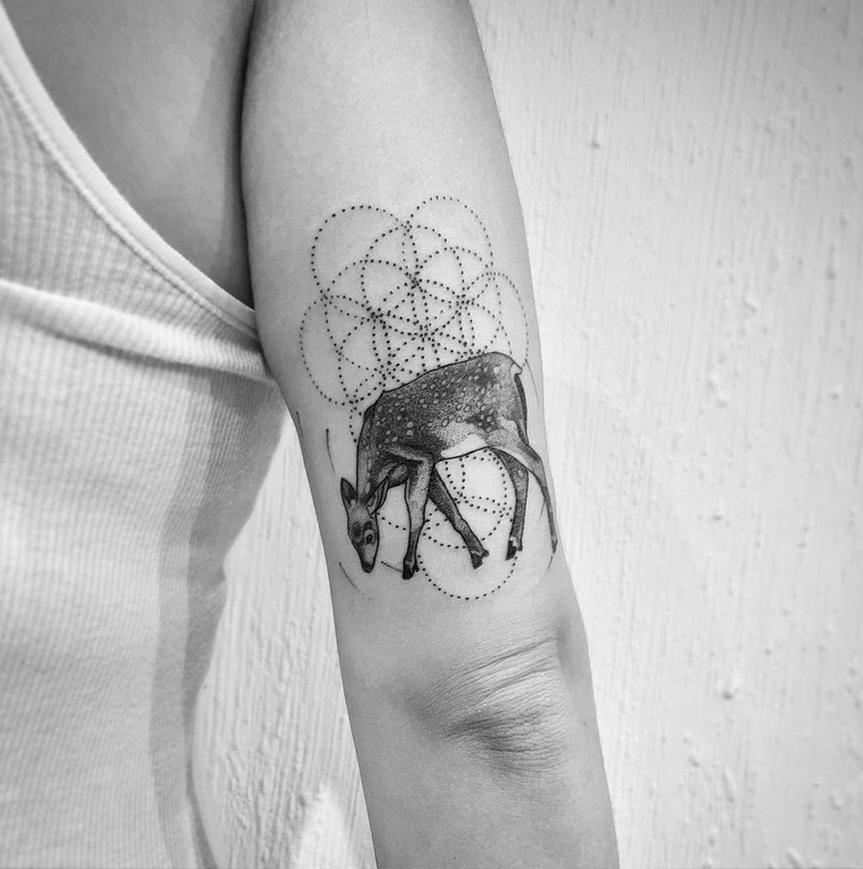 Natural looking black ink arm tattoo of deer with circles