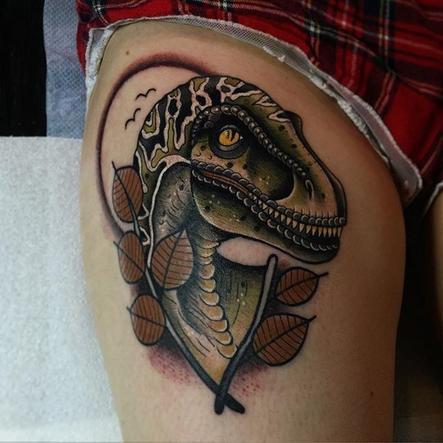 New school style colored thigh tattoo of dinosaur with leaves