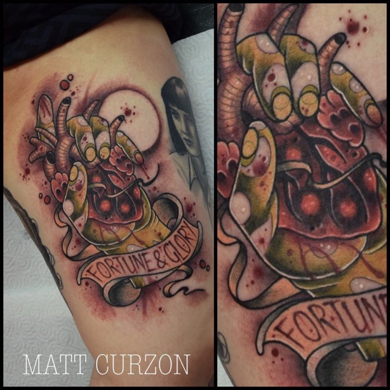 New school style colored thigh tattoo of zombie hand with bloody heart and lettering