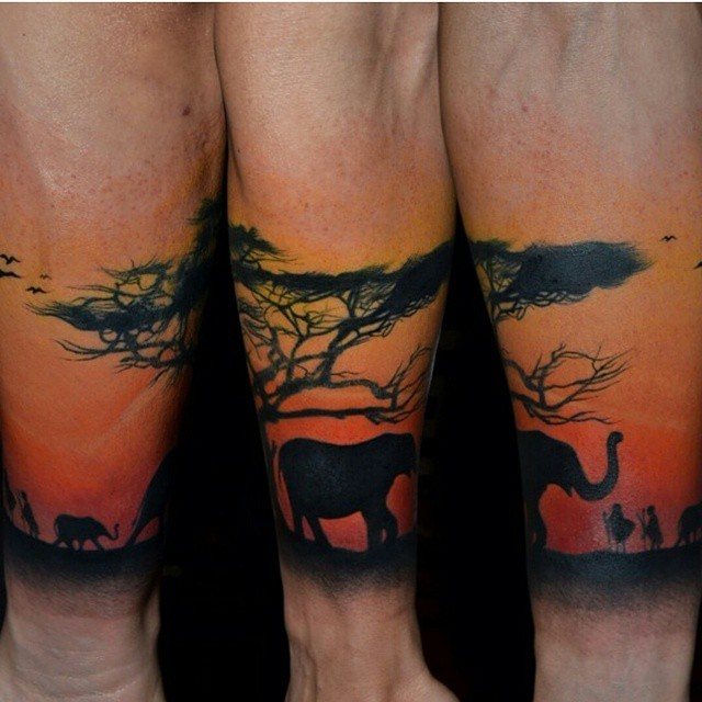 Nice looking colored forearm tattoo of desert tree with elephant