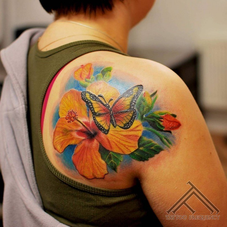 Nice looking colored scapular tattoo of beautiful lily with butterfly