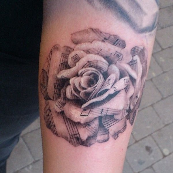 Nice music themed very detailed black and white rose tattoo on arm