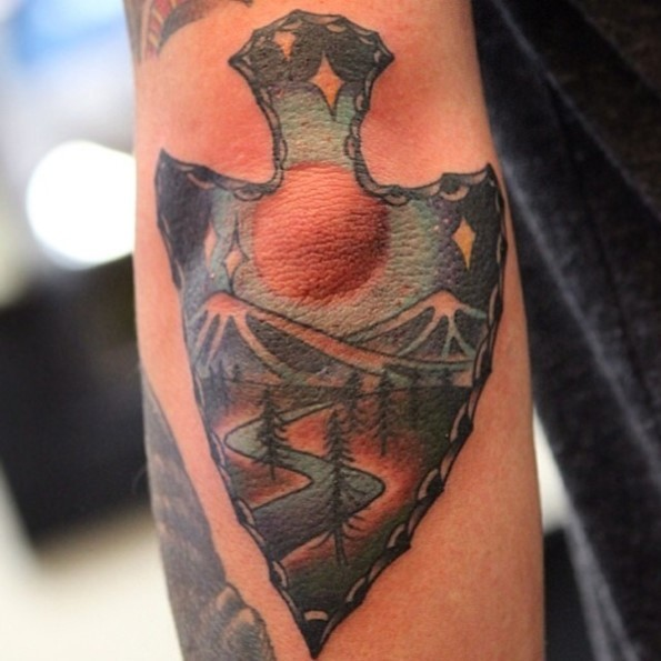 Old school designed colored ancient weapon on elbow tattoo stylized with night mountains