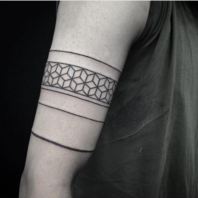 Old school style black ink biceps tattoo of geometrical ornaments