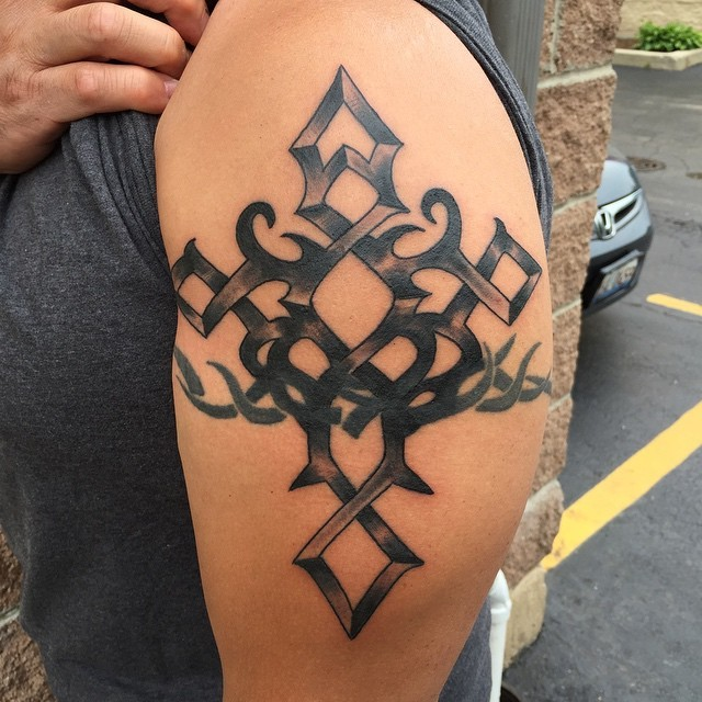 Old school style black ink cross shaped tattoo on upper arm