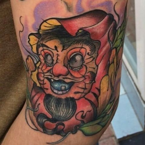 Old school style colored arm tattoo of funny daruma doll with leaves
