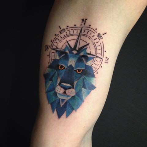 Old school style colored arm tattoo of blue lion head with compass