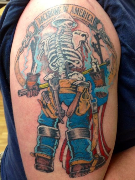 Old school style colored shoulder tattoo of lineman skeleton with lettering and flag