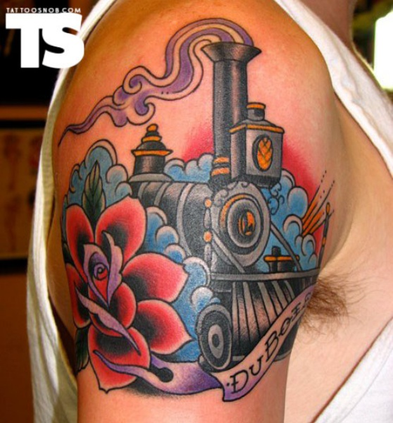Old school style colored train with flowers tattoo on shoulder stylized with lettering