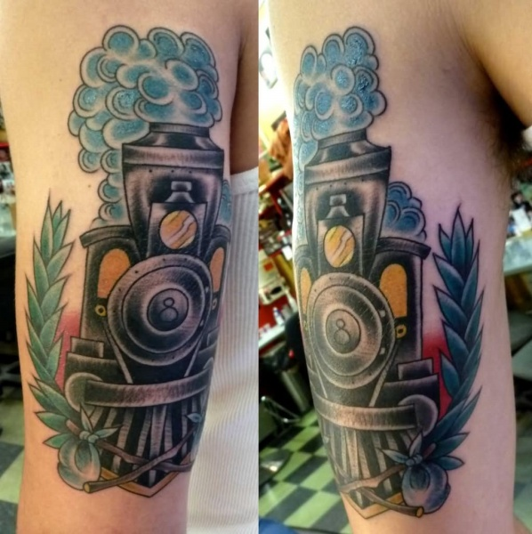 Old school style colored upper arm tattoo of old train with blue leafs