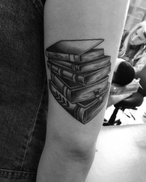 Pale of books with bookmarks tattoo near elbow