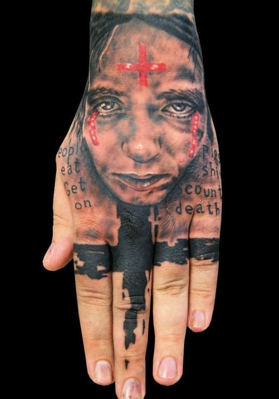 Photoshop style colored hand tattoo of woman face with red cross and lettering