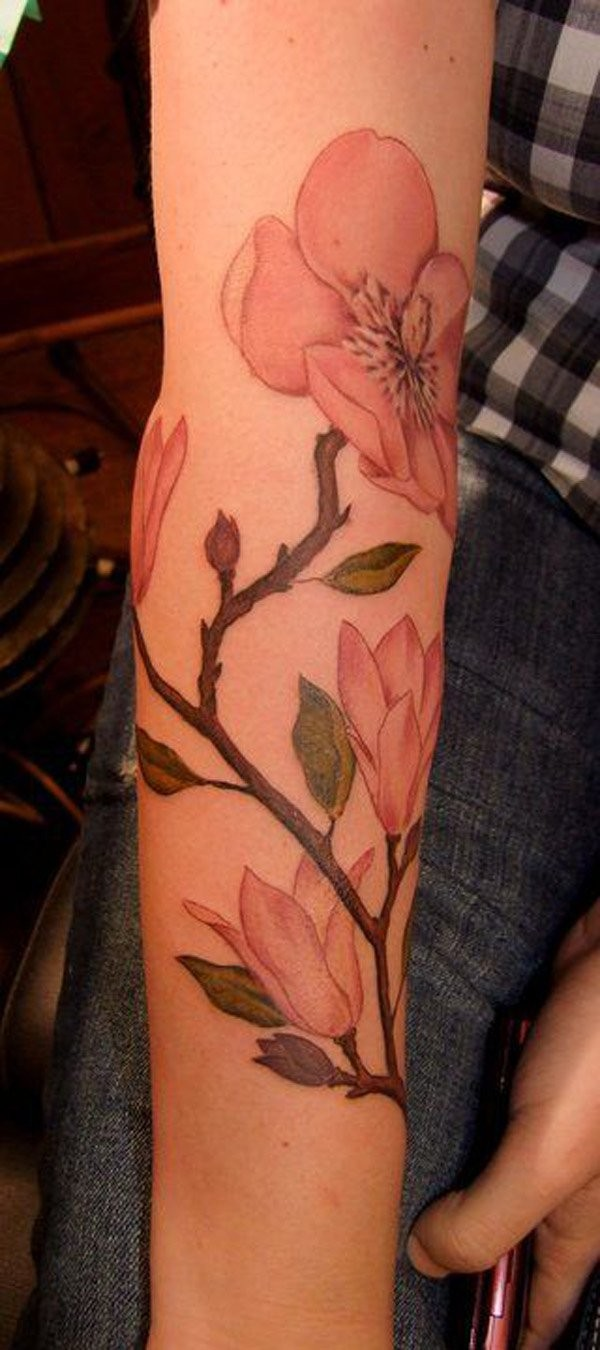 Pink colored illustrative style arm tattoo of big flowers branch