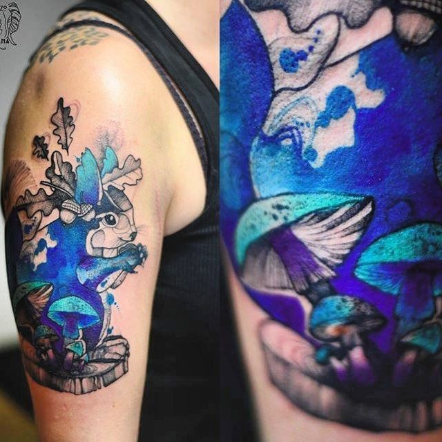 Psychedelic like colored upper arm tattoo of small squirrel with leaves