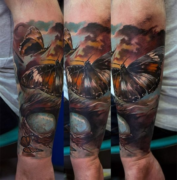 Realism style colored arm tattoo of big butterfly with bloody eye